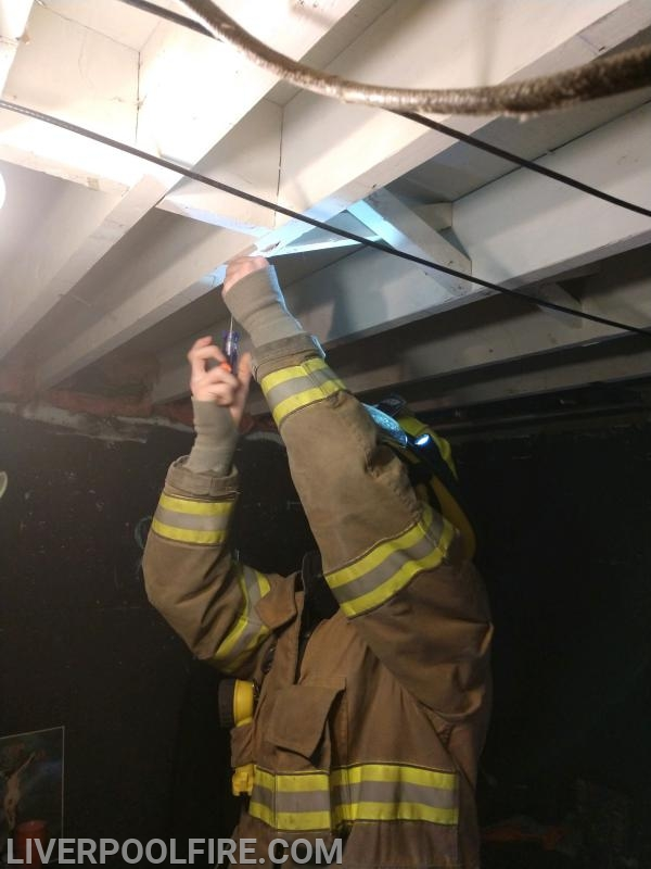 Firefighter/Bunk-in Dalton Majors installing a smoke detector